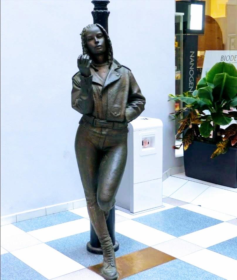 Statua di ragazza con mela appoggiata ad un lampione