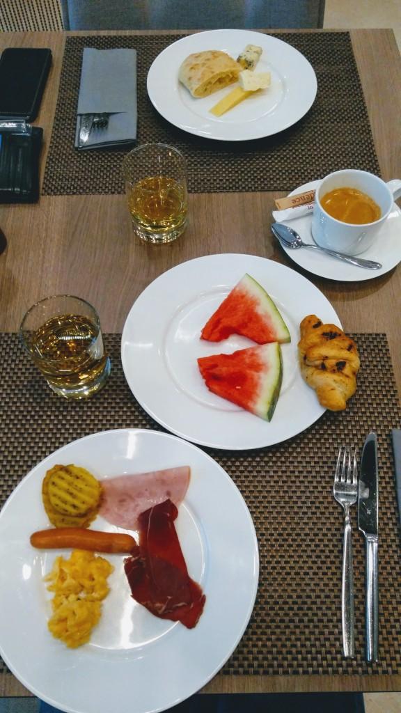 Piatto con due fette di anguria, croissant; secondo piatto con prosciutto, manzo affumicato, wurstel, tortino di patate e uovo strapazzato
