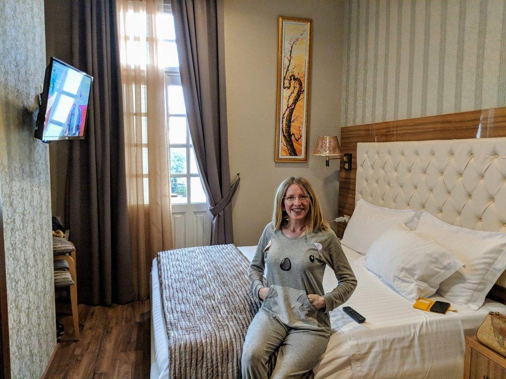 Gio seduta sul letto nella camera dell'Hotel Gloria a Tirana